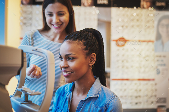 Smiling young black woman ready to take eye exam - Stock Photo - Images