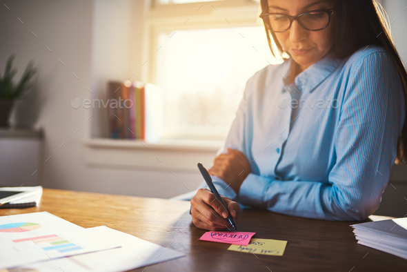 Business woman writing notes on post it - Stock Photo - Images