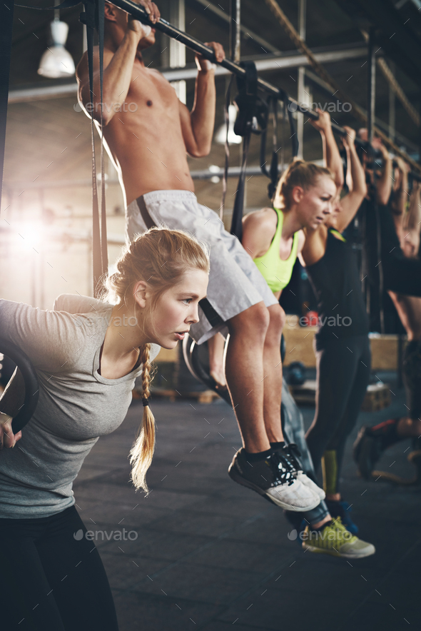 Men and women doing pull ups on bar in gym - Stock Photo - Images