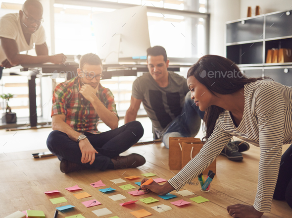 Group of workers sitting around notes on floor - Stock Photo - Images
