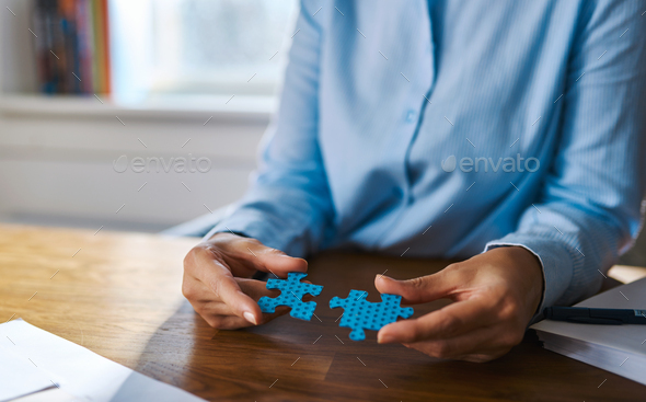 Close up of hands assembling two puzzle pieces - Stock Photo - Images