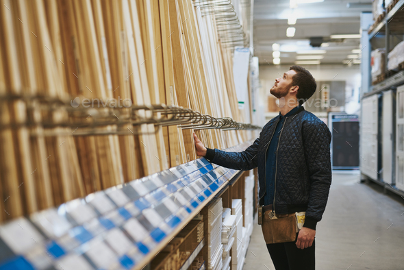 Carpenter selecting wood in a hardware store - Stock Photo - Images