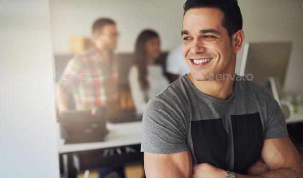 Smiling athletic man in office with co-workers - Stock Photo - Images