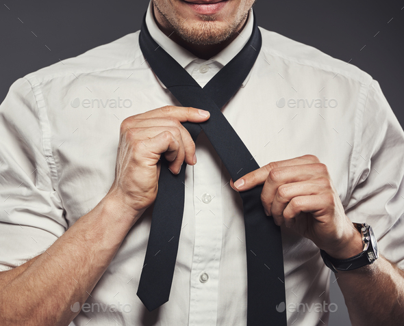 Young businessman tying his necktie for the business day - Stock Photo - Images