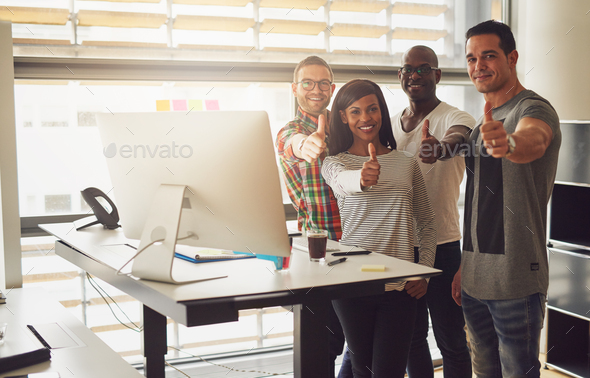 Cheerful office team standing with thumbs up - Stock Photo - Images
