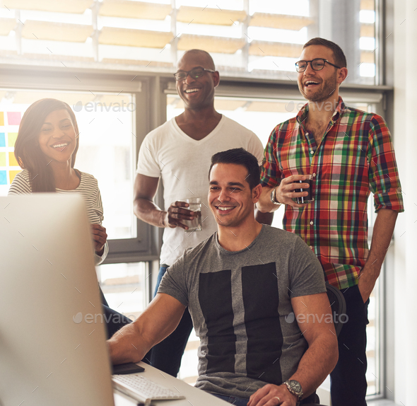 Happy quartet of young adults at desk - Stock Photo - Images