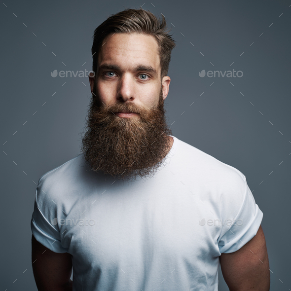 Serious young muscular man with large fuzzy beard - Stock Photo - Images