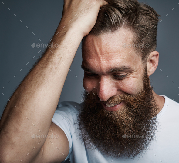 Bearded young man with a hand in his hair smiling - Stock Photo - Images
