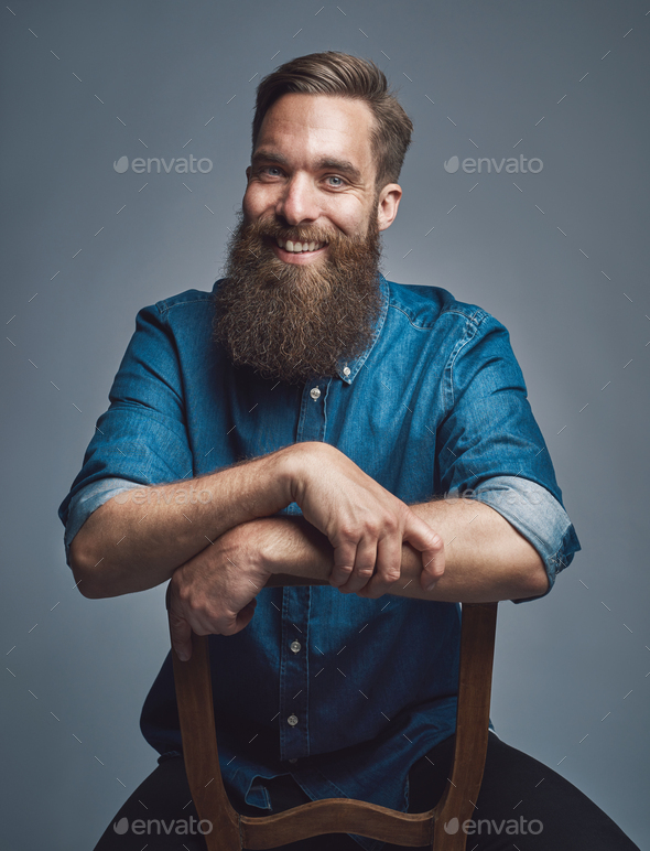 Laughing man with arms on back of chair over gray - Stock Photo - Images