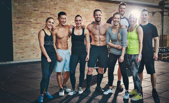 Group of eight athletic young adults in gym - Stock Photo - Images