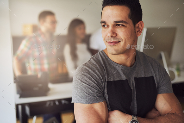 Calm muscular man in office with co-workers - Stock Photo - Images