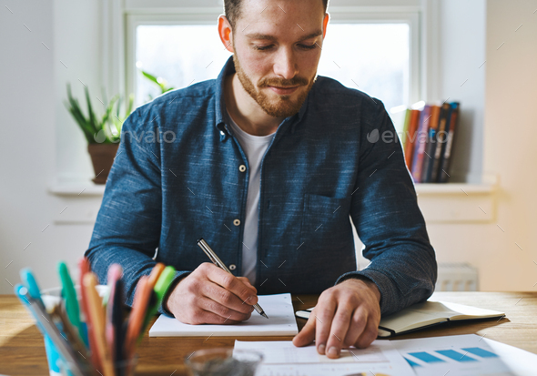 Man checking notes at home office - Stock Photo - Images