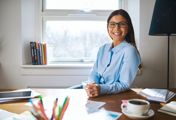 Self employed woman wearing glasses at desk - Stock Photo - Images