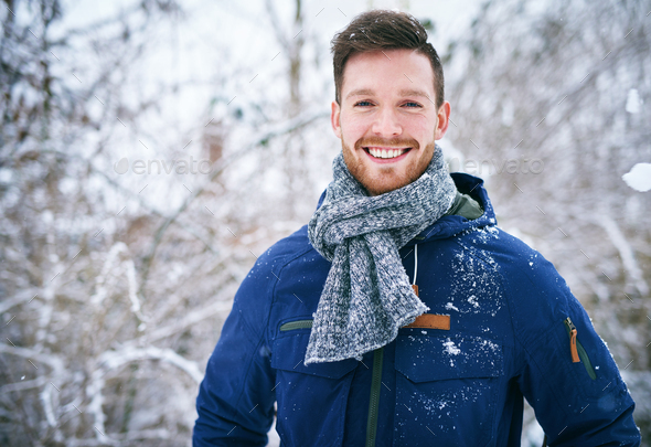 Young man in coat standing in snowfall - Stock Photo - Images