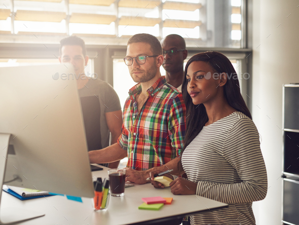 Four diverse workers standing next to computer - Stock Photo - Images