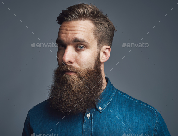 Bearded young hipster standing alone against a gray background - Stock Photo - Images