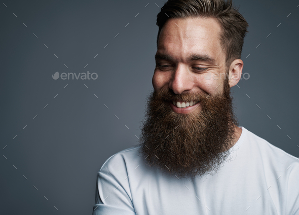 Smiling bearded hipster standing against a gray background - Stock Photo - Images