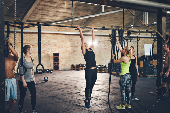 Adults doing pull ups on bar in gym - Stock Photo - Images