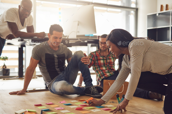 Group of employees meeting around notes on floor - Stock Photo - Images