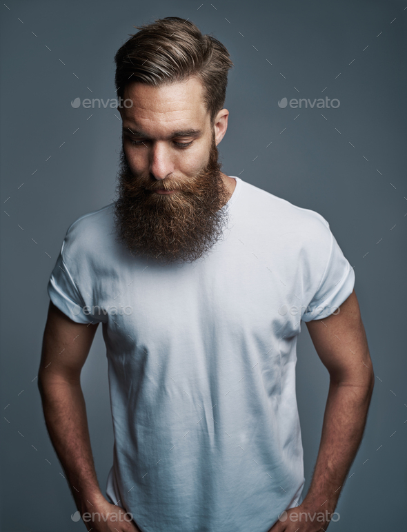 Bearded young man standing alone against a gray background - Stock Photo - Images