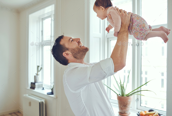 Loving father holding his baby girl up in the air - Stock Photo - Images