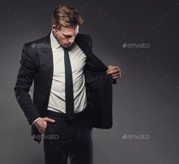 Young businessman in a stylish suit aganst a grey background - Stock Photo - Images