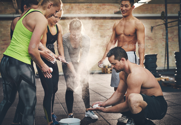 Athletic adults applying talcum powder to hands - Stock Photo - Images