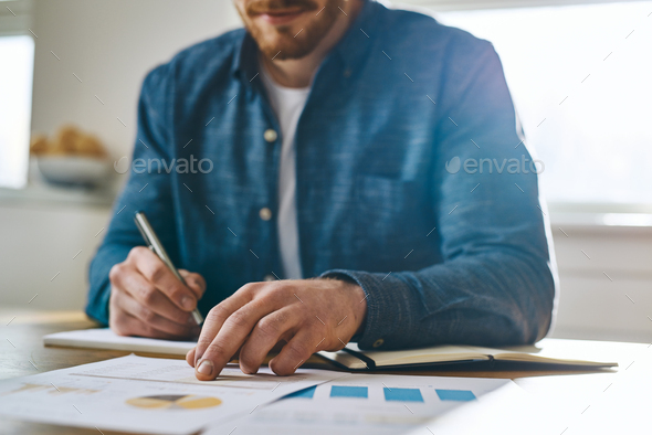 Focused view of hand over paperwork - Stock Photo - Images