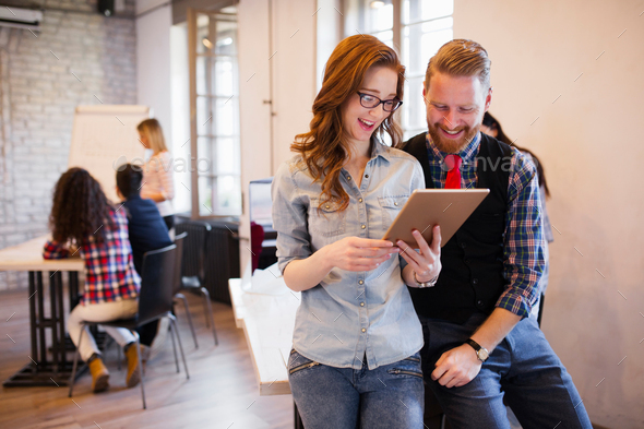 Young attractive designers talking and looking at digital tablet - Stock Photo - Images