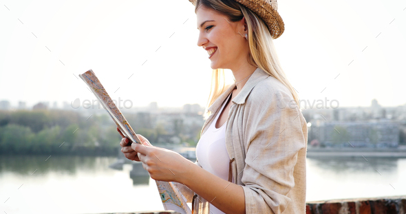 Tourist woman holding travelers map to travel to destination - Stock Photo - Images