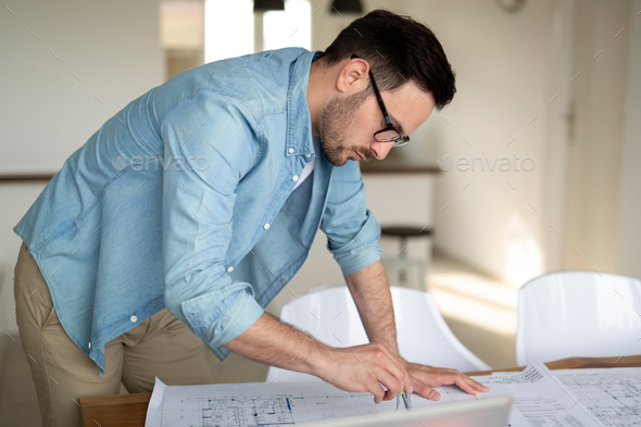Architect working on drawing table in office - Stock Photo - Images