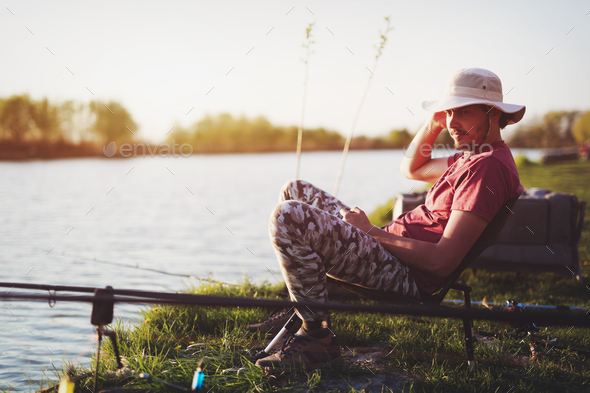 Men fishing in sunset and relaxing while enjoying hobby - Stock Photo - Images