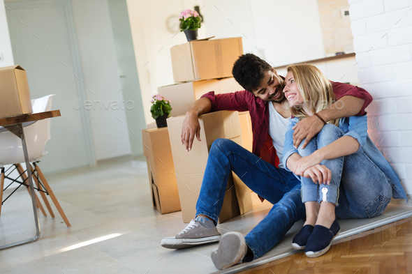 Young married couple with boxes and holding flat keys - Stock Photo - Images