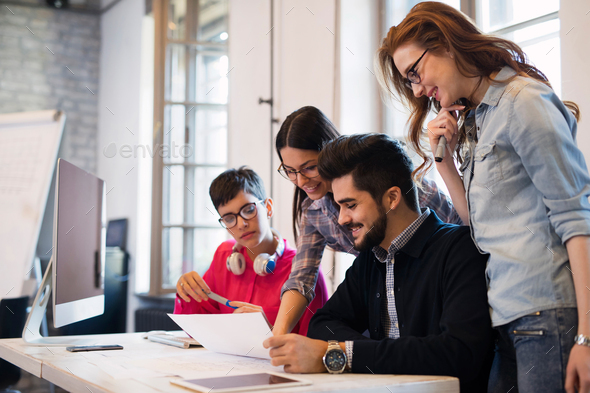 Group of young perspective architects looking at project papers - Stock Photo - Images