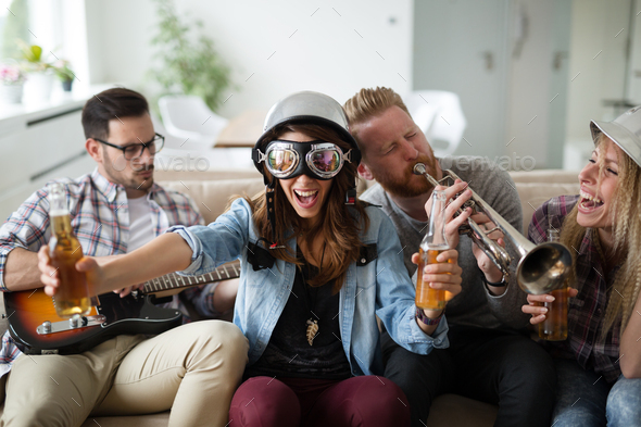 Happy group of friends playing instruments and partying - Stock Photo - Images