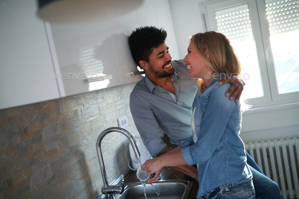 Young couple doing dishes in the kitchen and smiling - Stock Photo - Images