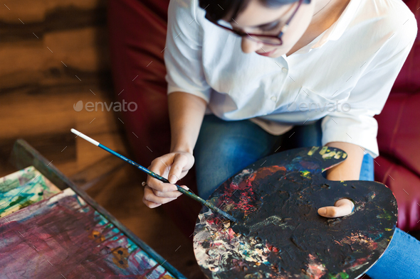 Creative pensive art school painter working on painting - Stock Photo - Images