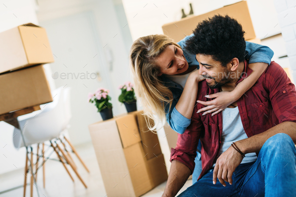home, people, moving and real estate concept - happy couple having fun while moving in - Stock Photo - Images