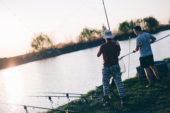 Young man fishing on a lake at sunset and enjoying hobby - Stock Photo - Images