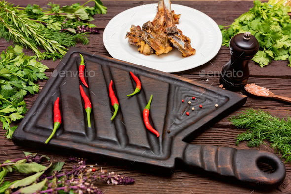 Roasted lamb ribs served on plate and cutting board with chili pepper - Stock Photo - Images