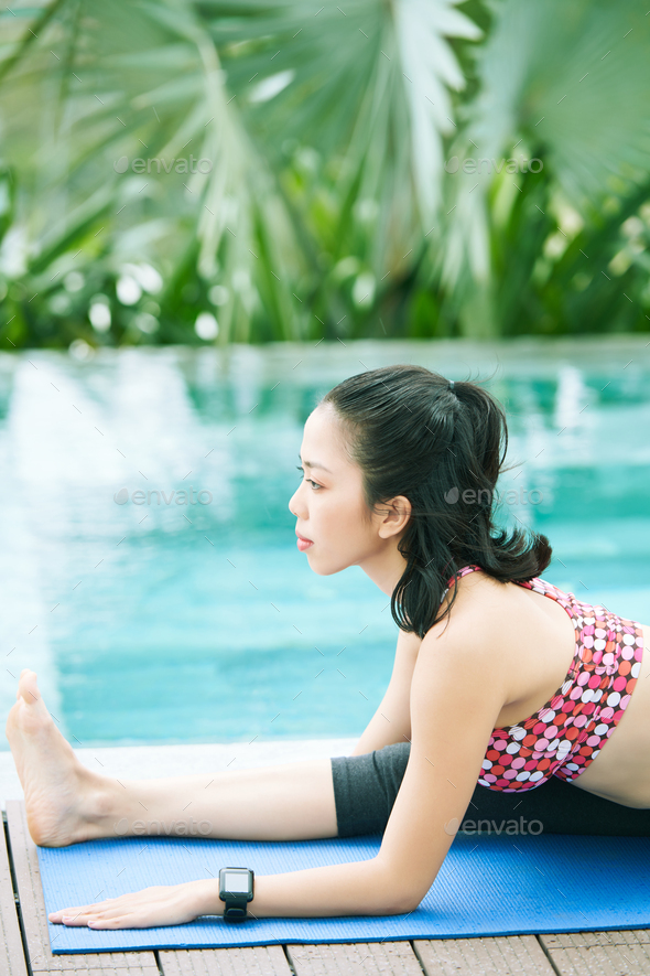 Woman stretching near the poolside - Stock Photo - Images