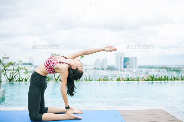 Asian fit woman exercising at the poolside - Stock Photo - Images