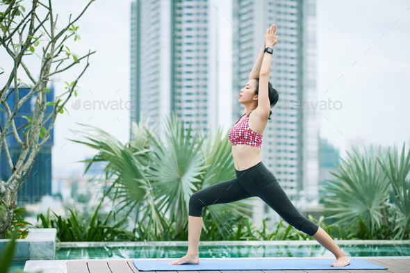 Asian woman doing yoga in the city - Stock Photo - Images