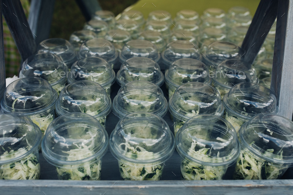 Organic veggies in cups to go.Close-up of loads of plastic cups filled with chopped vegetables and - Stock Photo - Images