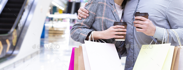 Loving couple shopping in mall with coffee, holding paper bags - Stock Photo - Images