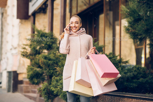 Happy fashion woman talking on cellphone after shopping - Stock Photo - Images