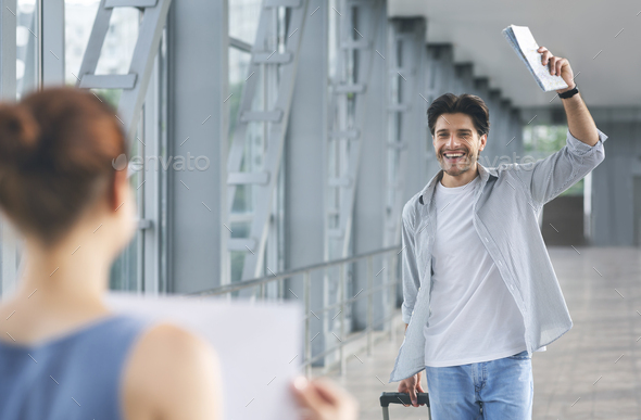 Passenger walking with luggage to woman with name board - Stock Photo - Images