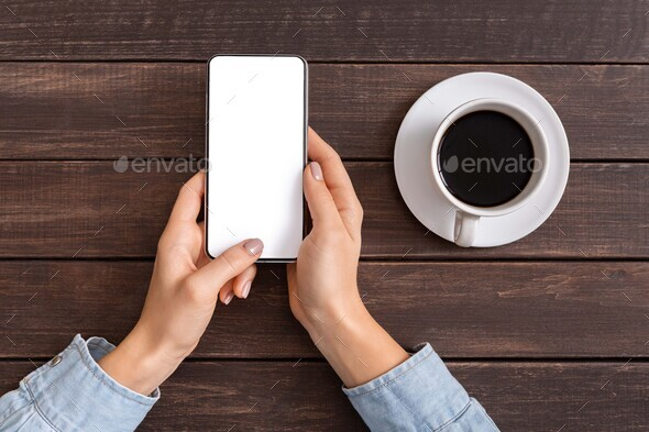 Woman reading message on smartphone while drinking coffee - Stock Photo - Images
