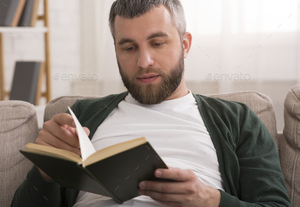 Middle aged man reading book at home - Stock Photo - Images