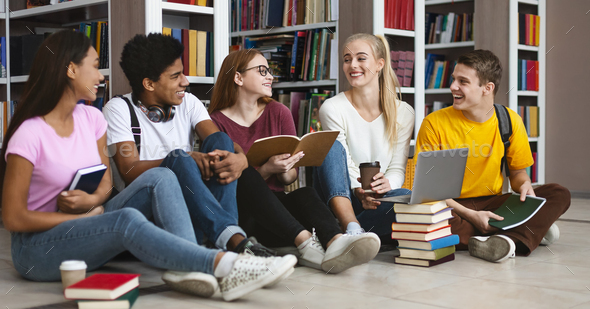 Group of international students talking over homework - Stock Photo - Images